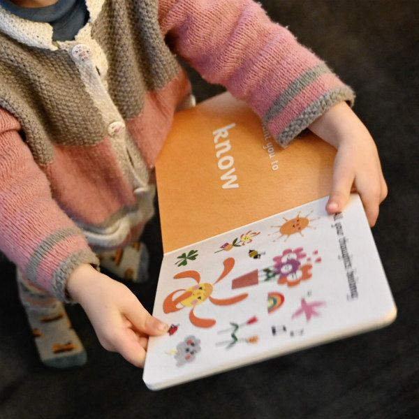 toddler holding board book