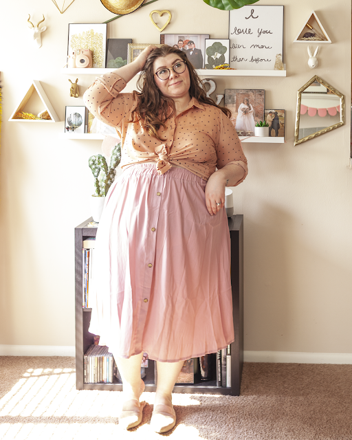 An outfit consisting of a muted pink button down blouse with the sleeves rolled up and tied at the waist and a pink pleated midi skirt and muted pink pointed toe mules.