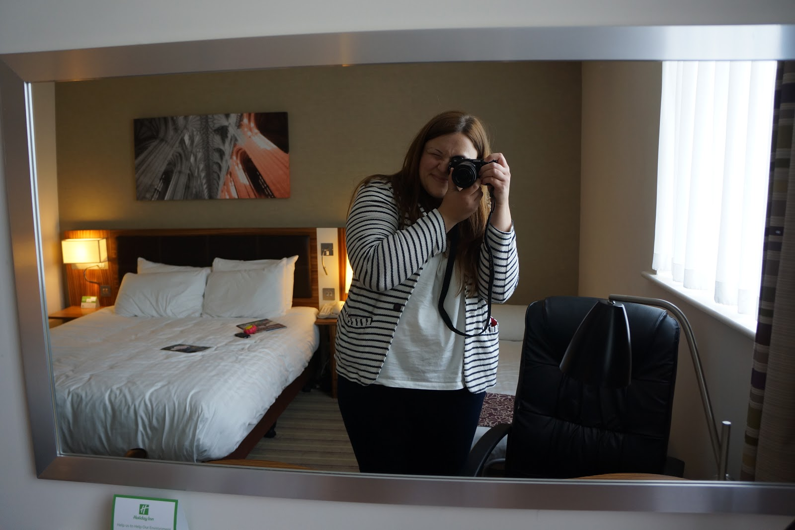 a mirror and a picture of a hotel room