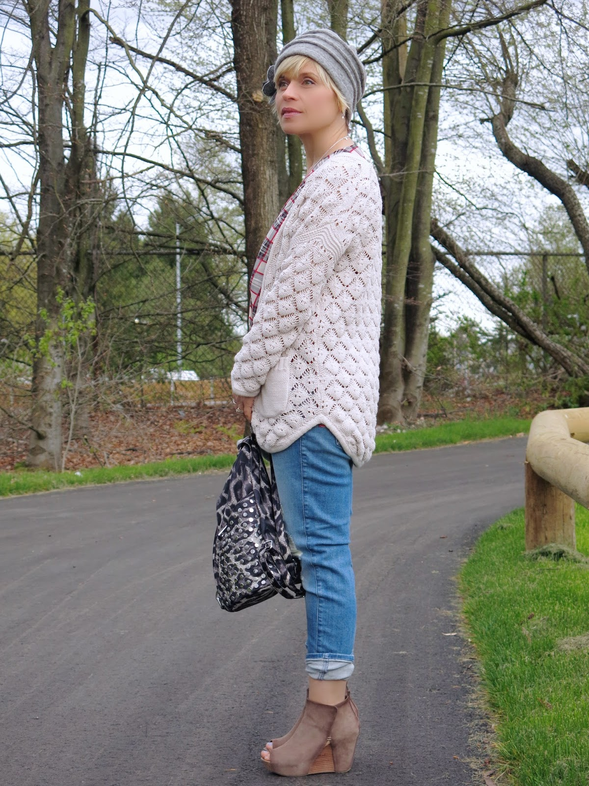 boyfriend jeans styled with a plaid top, grandpa cardigan, and felt-flower hat