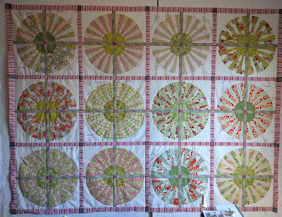 Wheel composed of four fan blocks with alternating pale red and green blades sashed with tan are in turn sashed with red and white stripe in this low volume quilt