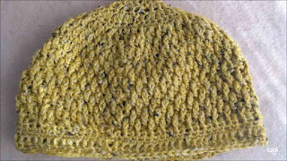 A crochet hat done in a textured stitch.  The hat is mustard-yellow with small flecks of black.