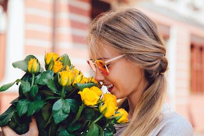 Mujer oliendo las flores