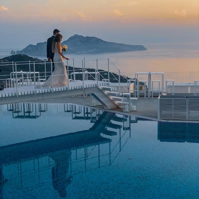 Sorrento, Villa Eliana. Capri sullo sfondo e gli sposi sulla passerella in piscina. Alessia Siena