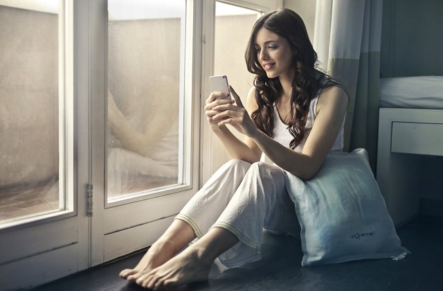 woman sitting by the window seat looking on phone smiling