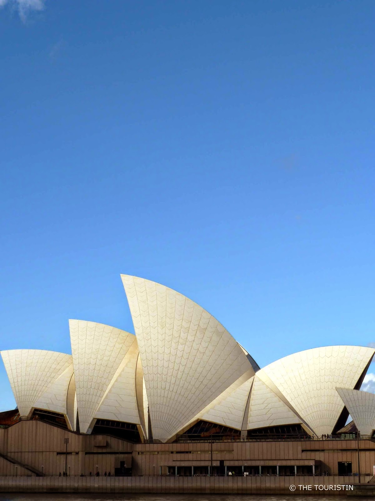The glossy white and matte cream tiled and decorated sails of a performing arts centre (Sydney Opera House) under a big blue sky.