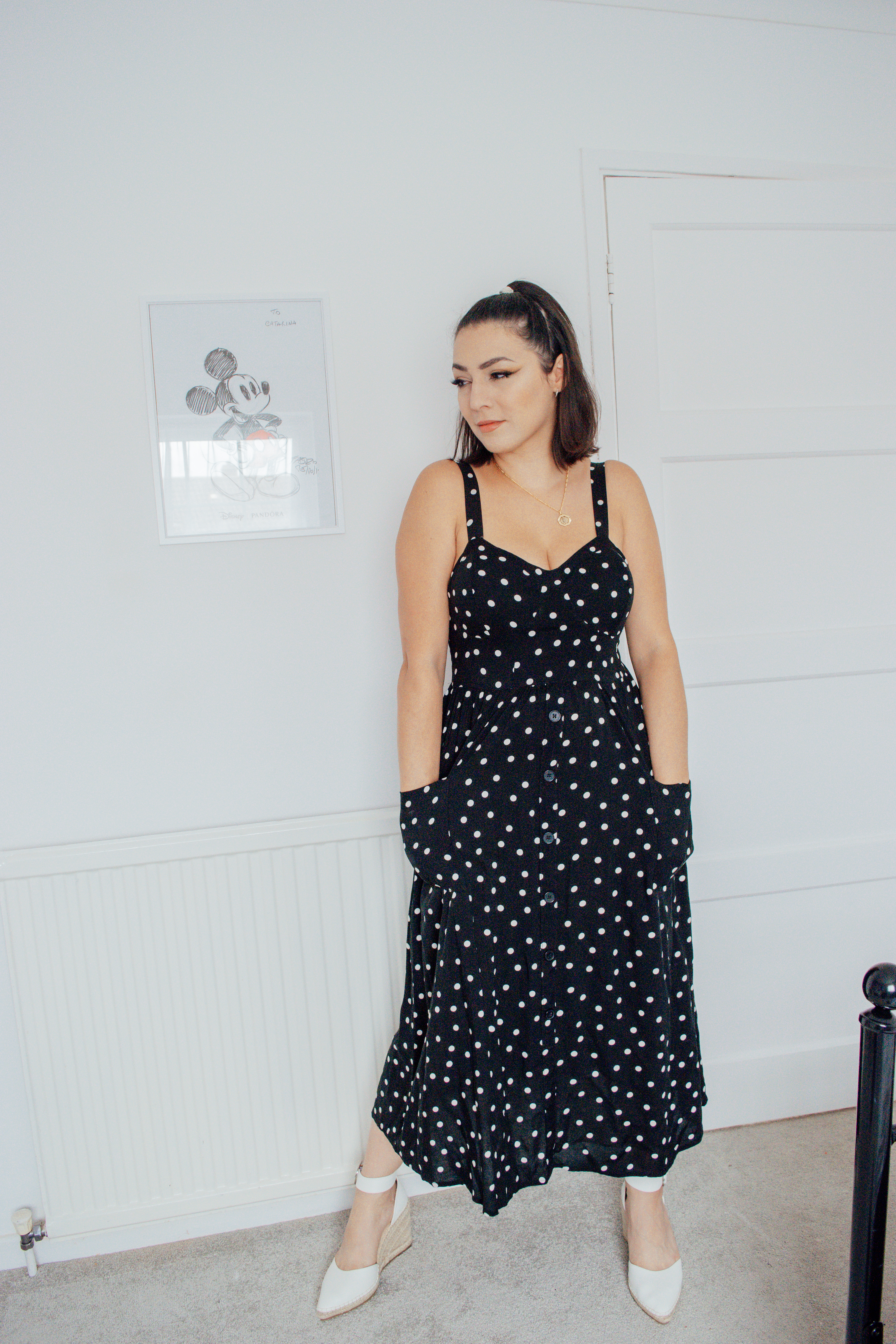 Girl wearing a black polka dot midi dress with hands in pockets