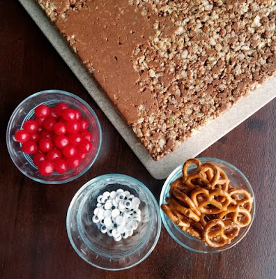 chocolate peanut butter rice krispies with bowls of pretzels, eyes and sour cherry candy