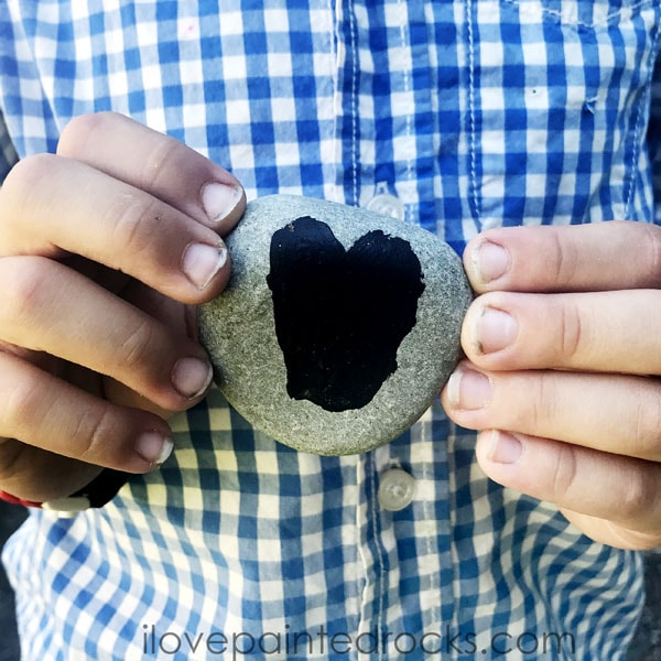 boy holding a painted rock with a black heart on it - how to seal painted rocks for hiding outdoors