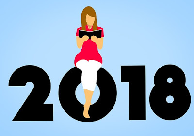 woman reading, sitting on a big '2018'