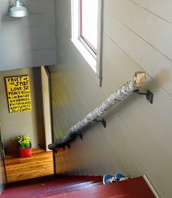 Pasamanos para bajar las escaleras hecho con un tronco reciclado