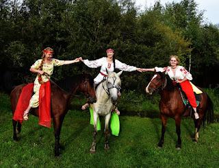 Три девушки в славянских платьях сидят на лошадях