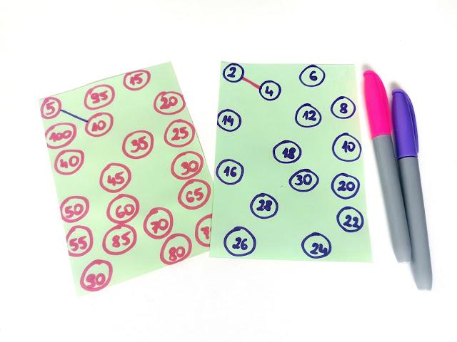 na zdjęciu dwie zielone kartki a na nich liczby będące wielokrotnością 2 i 5 które trzeba połączyć liniami, obok leżą dwa mazaki