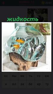 в аквариуме находится жидкость с рыбками на столе