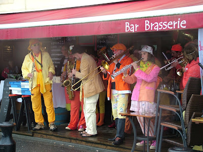 brightly dressed group of musicians performing in front of a brasserie