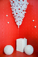 A Christmas decoration of a small white upside-down Christmas tree on a red background complimented by white candles
