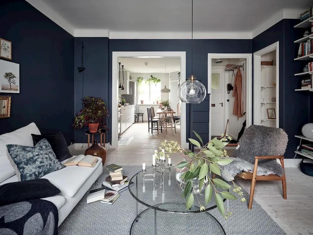Salón con pared azul y marcos de puertas blancos