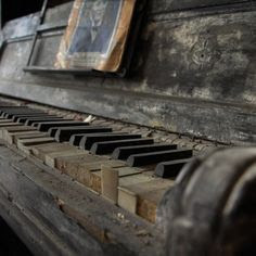 An old disused dusty close up shot of a piano keys, with a photo of someone on the music sheet stand