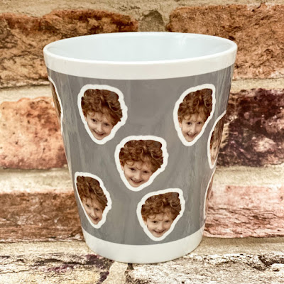 A small grey plant pot with small pictures of a child's smiley face