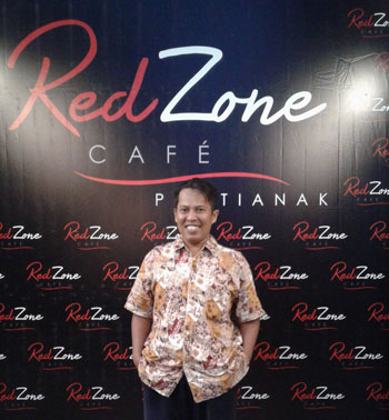 The writer in front of the Pontianak Red Zone Cafe booth. Special photo