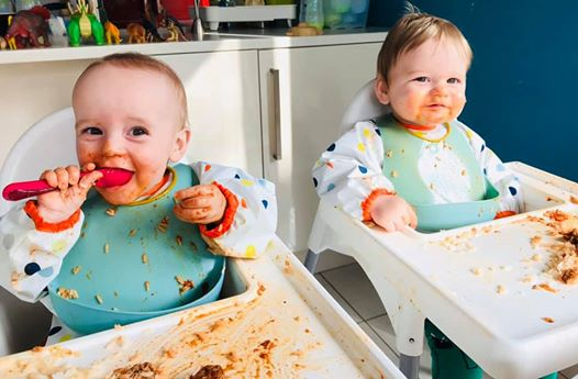 twins sitting in ikea antiplop highchairs with coverall bibs and scoop bibs covered in mess. One has a spoon in their mouth
