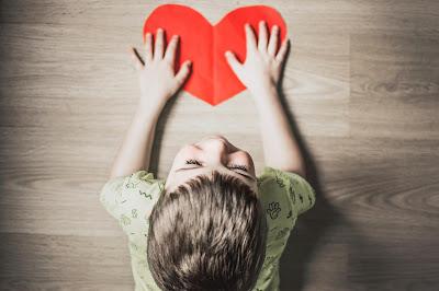 Niño con un corazón recortado en un papel rojo