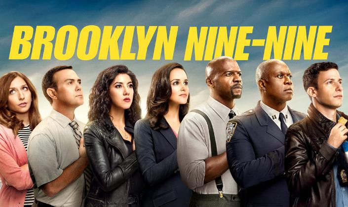 """Imagem de capa: os personagens da série Brooklyn 99, da direita para a esquerda, Gina, em um casaco rosa com camisa listrada preta e branca, Boyle, com uma roupa cor de malva e uma gravata, Rosa, com um casaco de couro e camisa preta, Amy, em um terno cinza--escuro com uma blusa cor de salmão, os cabelos presos, Terry, um homem negro e careca, alto e com suspensórios, Holt, um homem negro e careca de meia-idade, baixo e em uniforme da polícia e Jake, um homem branco num casacode couro com o distintivo policial no pescoço, todos em fila, com a mão no peito, olhando em diversas direções e acima a logo da série em amarelo-canário, como a fita de isolamento policial que diz """"Brooklyn 99"""" sobre o fundo azul."""