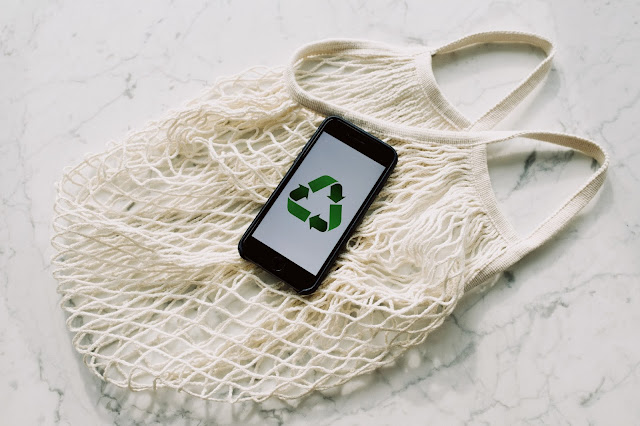 There is a white marble table with a white netted shopping back on top. The bag is reusable. In the centre of the image, on top of the bag, there is a black iphone which has the recycling image on the screen