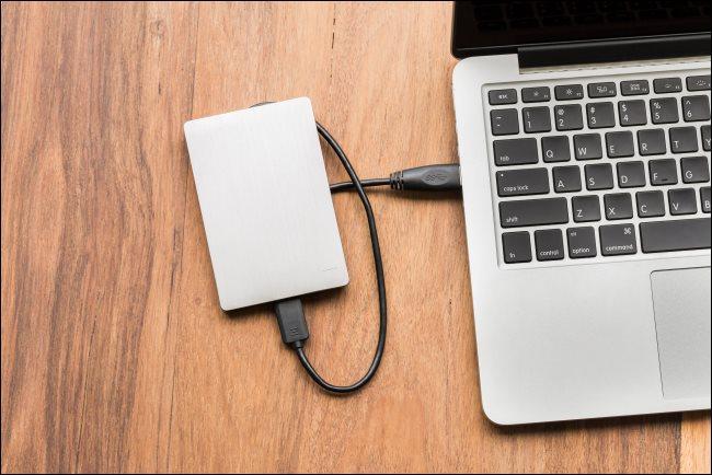 قرص صلب USB متصل بجهاز كمبيوتر محمول.