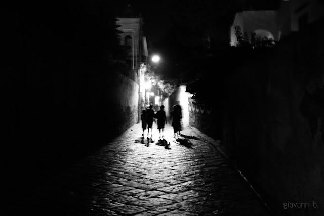 Gruppo di persone che cammina di notte in un vicolo
