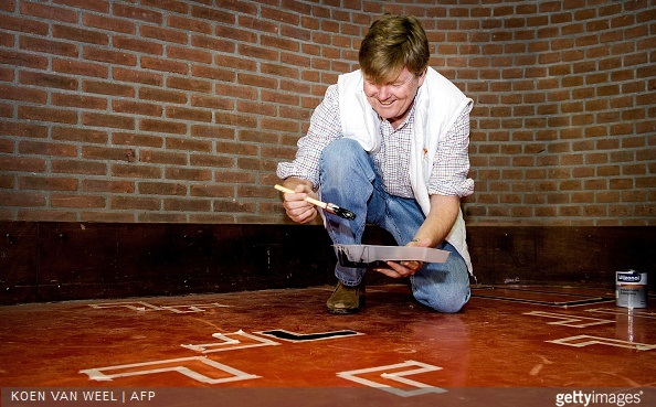 Dutch King Willem Alexander paints the floor in the sports area of a cultural centre in the village Tricht, on March 21, 2015. Members of the Dutch royal family take part in the national voluntary event NLdoet.
