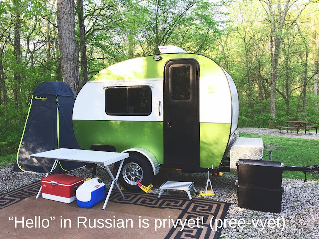 Tiny teardrop trailer camping with outdoor cooking station and utilitent