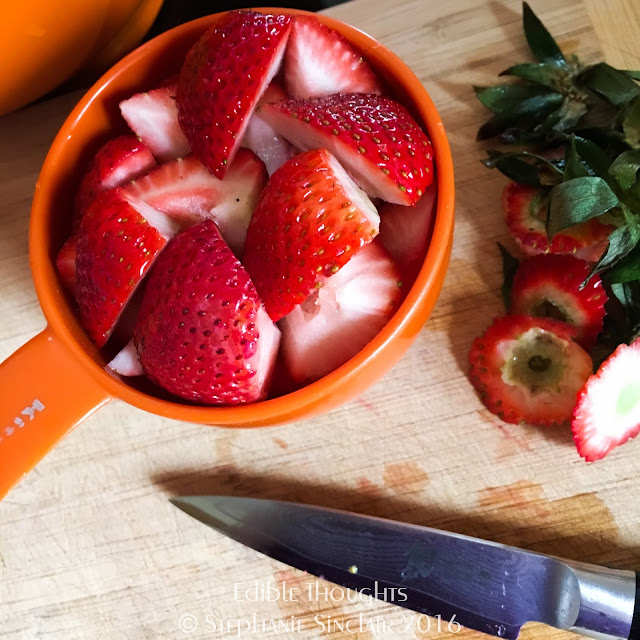 Image of an orange measuring cup with cut up strawberries sitting on a bamboo cutting board next to a paring knife and tops of strawberries.