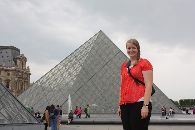 Meagan in front of a glass pyramid at the Louvre