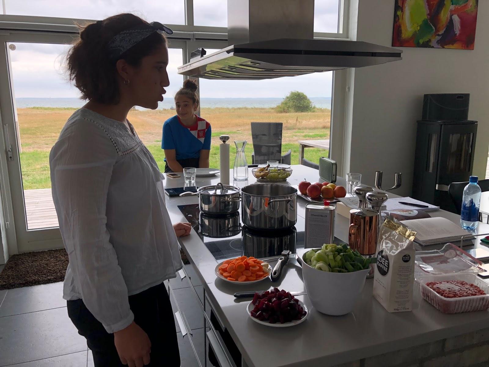 Sophie und Clara machen Grimassen beim Kochen. Kegnaes, Dänemark