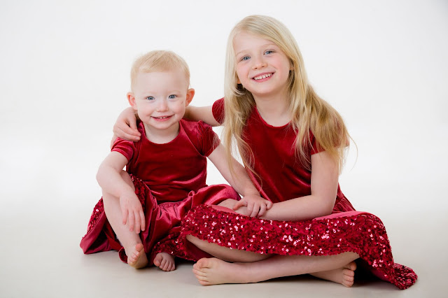 two sisters in party dresses sitting on the floor and smiling