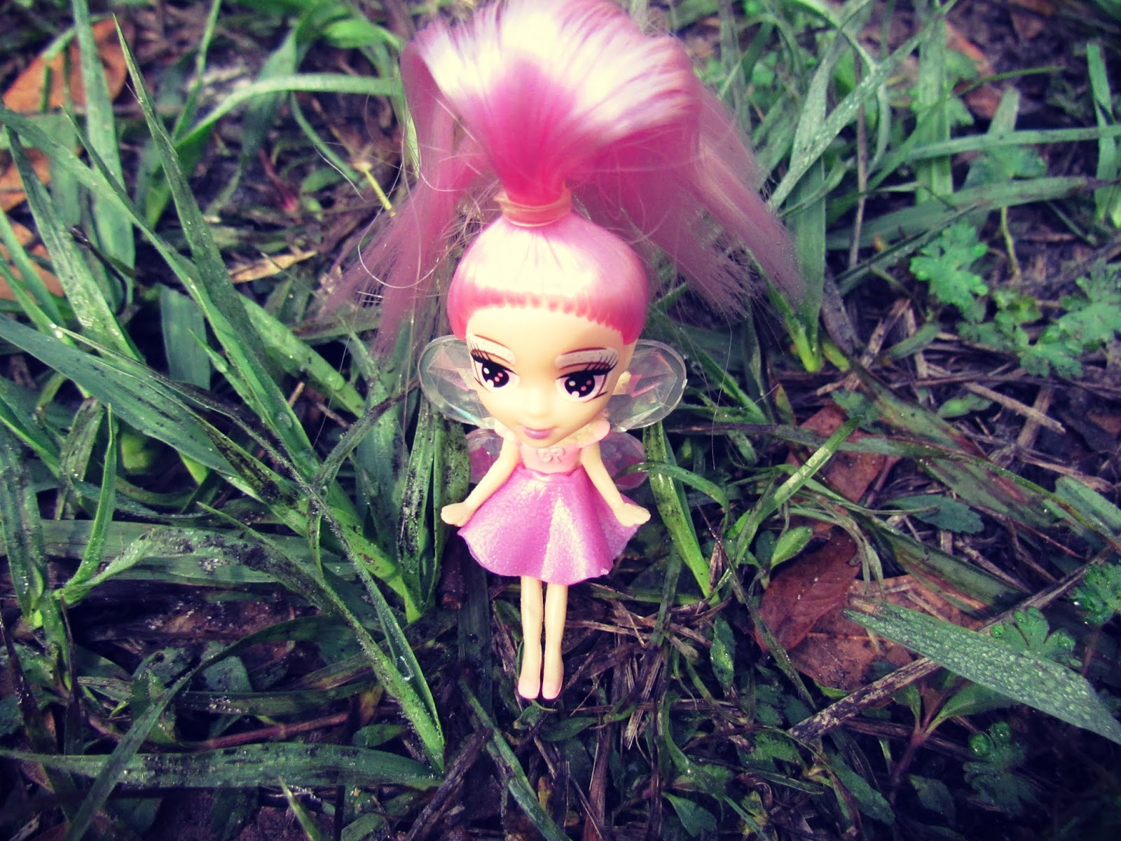 A Pink-haired plastic fairy doll ring in the green tall grass in a meadow in Florida wildlife