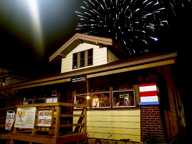 color night-time view of Grafton Illinois coffee antiques shop Lightkeepers Coffee 101 E Main St Sears Vallonia with 4th of July fireworks