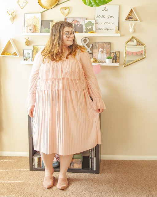 An outfit consisting of a pastel pink blouse with coordinated polka dots with sheer organza layers and long sleeves over a pastel pink pleated midi skirt and muted pink pointed toe mules.