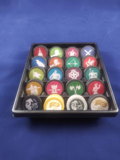 A tray containing the different tokens: black tokens with a Celtic knot raven, yellow tokens with a Celtic knot wolf head, deep yellow tokens with pikeman holding a shield, magenta tokens with a castle tower and spear, dark green tokens with two crossed battle axes, crimson tokens with a Greek warrior, olive tokens with a banner, bright blue tokens with a knight carrying sword and shield, deep purple tokens with a Celtic cross, teal tokens with warriors carrying spear and shield, deep blue tokens with a hawk, amber tokens with a saddled horse, bright green tokens with a bow and arrow, bright red tokens with a soldier mounted on horseback carrying a lance, burgundy tokens with a dagger piercing a bag of coins, lime green tokens with a rearing horse, reddish violet tokens with a crossbow, and dark blue tokens with two crossed swords.