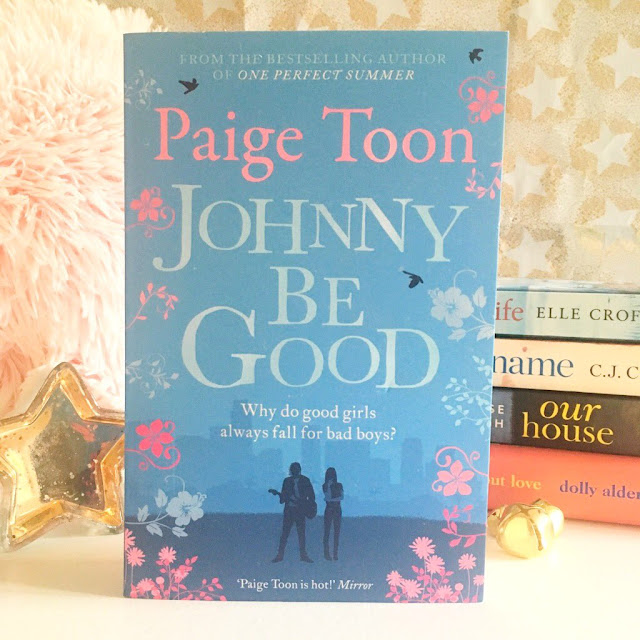 Johnny Be Good by Paige Toon in the centre. Pink fluffy pillow in the background on the left side. Stack of pink books at the book on the right side. A star trinket dish also in the photo