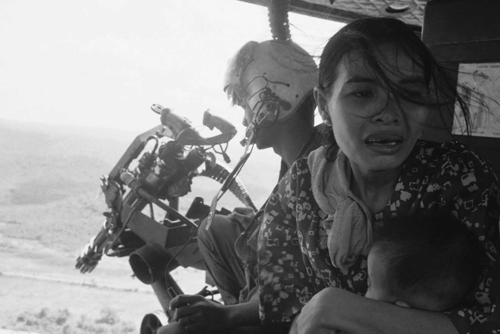 A refugee clutches her baby as a government helicopter gunship carries them away near Tuy Hoa, 235 miles northeast of Saigon on March 22, 1975. They were among thousands fleeing from recent Communist advances. With U.S. forces out of the country, North Vietnamese troops tested South Vietnamese defenses (and the willingness of the U.S. to return to the fight) starting in 1974, and began capturing territory.
