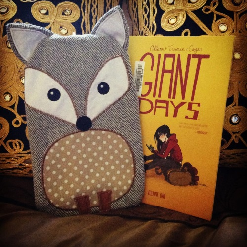 A water bottle shaped like a stylized grey fox leans upright against a pair of black and gold pillows, next to a trade paperback copy of Giant Days. The comic's cover features a white Goth-lite girl sitting on a dufflebag.