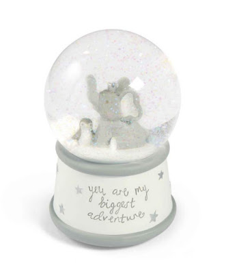 A snow globe in grey and white with an elephant and penguin inside with glittery white snow