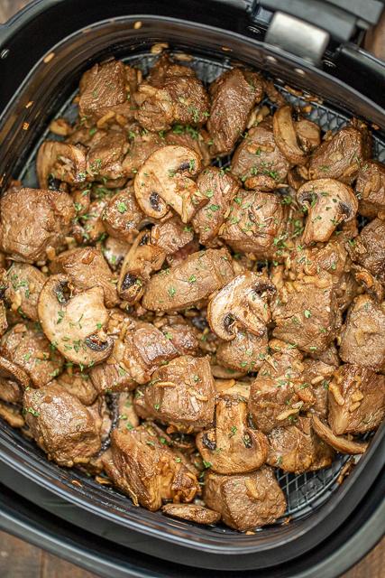 cooked steak and mushrooms in air fryer basket