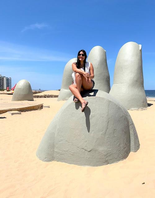 mulher em cima de um dedo de concreto de uma praia