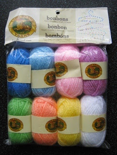Eight mini skeins in different colours laid out in two rows: dark blue, light blue, pale pink, lilac, light green, apricot, yellow and white.