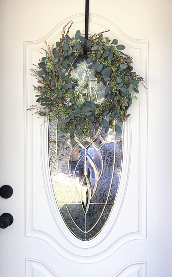 wreath on front door with oval window