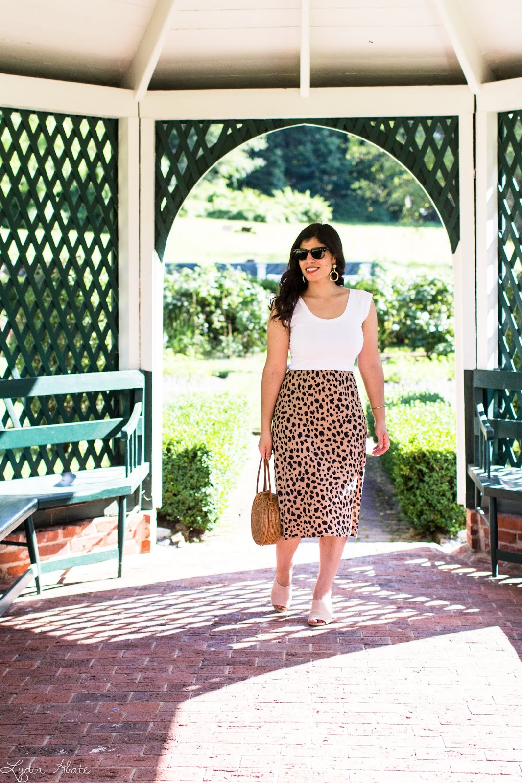 Connecticut style blogger Lydia Abate wearing a leopard midi skirt, white bodysuit, blush scalloped mules, round rattan bag, and gold hoop earrings for summer in New England