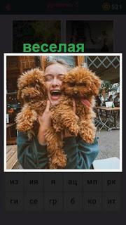 веселая девушка держит в руках двух одинаковых собак коричневого цвета
